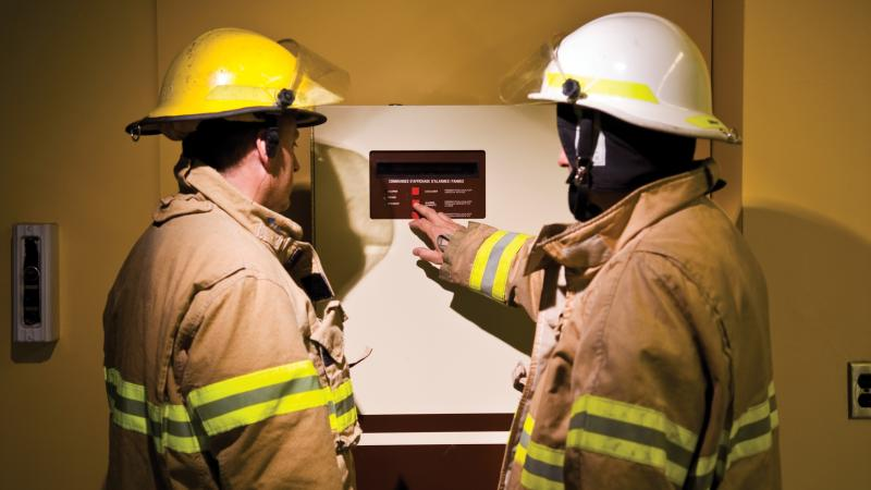 Two Montréal firefighters use the control panel