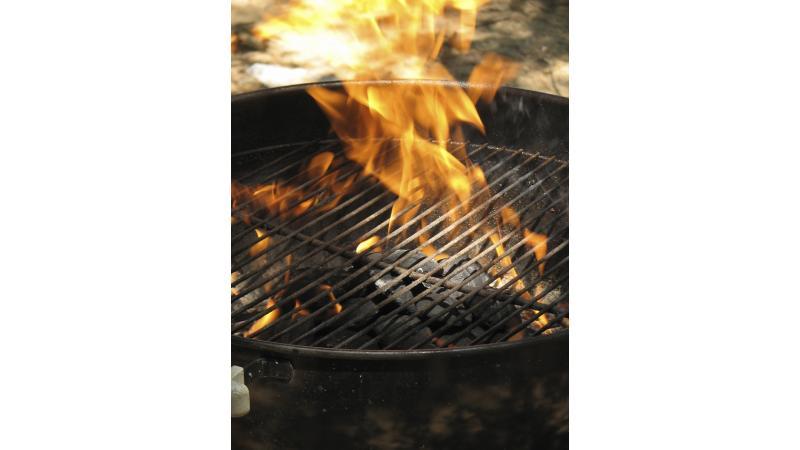 Des flammes jaillissent d'un appareil de cuisson extérieur.