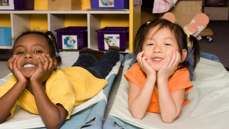 Two girls on folding cots at naptime