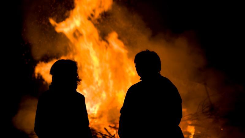 Deux individus devant un feu en plein-air.