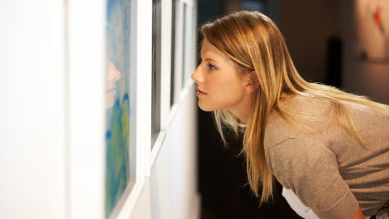 Une jeune femme contemple attentivement une œuvre d'art, lors d'une exposition.