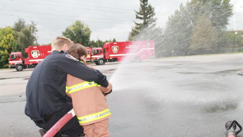 Un pompier en compagnie d'un jeune citoyen lors de la journée portes ouvertes à la caserne65.