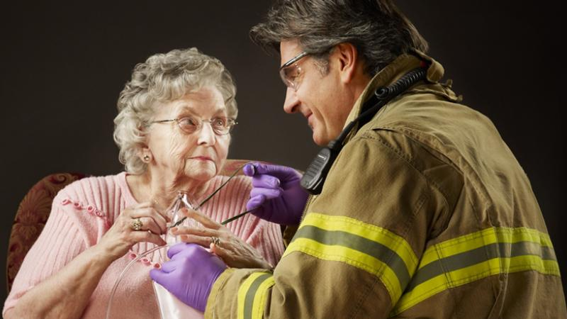 Firefighter/first responder assists a senior citizen