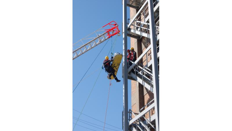 Trois pompiers en pleine simulation de sauvetage en hauteur.