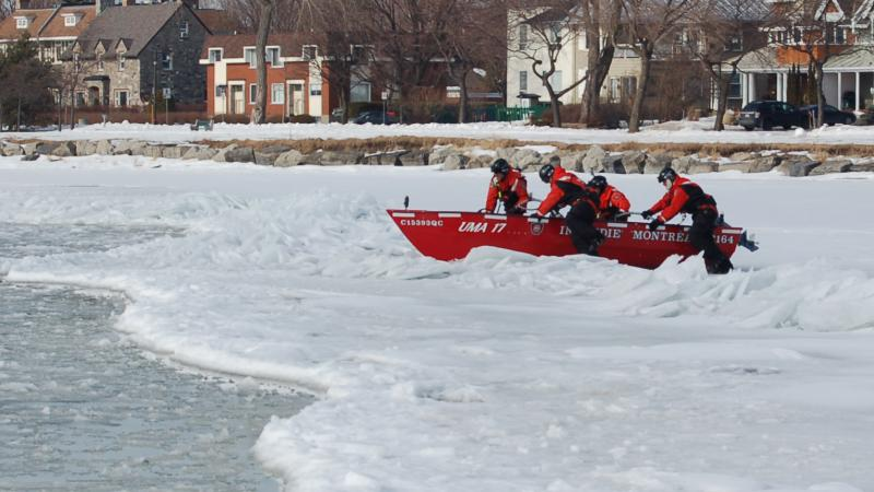 Firefighters-rescue workers in a boat during an ice rescue simulation