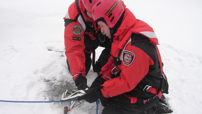 Two firefighters-rescue workers during an ice rescue simulation