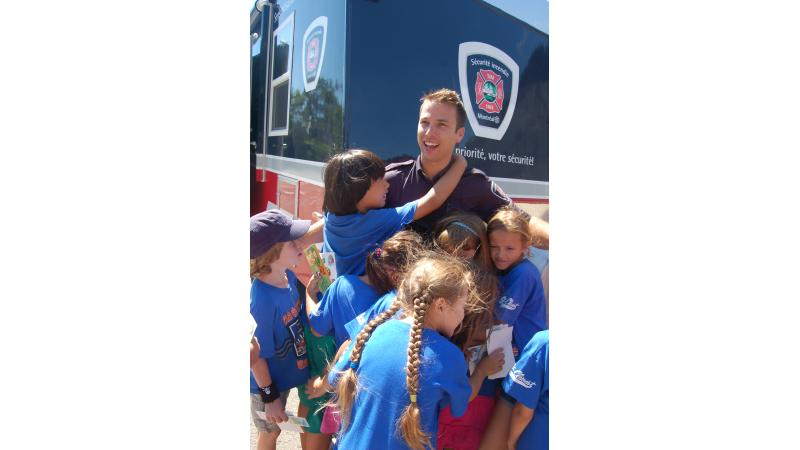 Children thank a fire safety educator for his visit