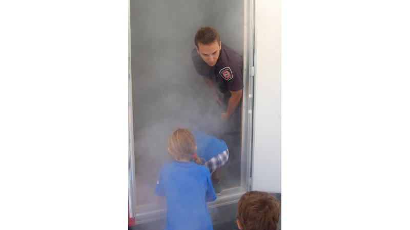 Coached by a fire safety educator, children evacuate the SIMulateur amid non-toxic smoke.