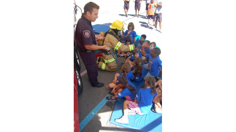 Two fire safety educators explain firefighters' work to children