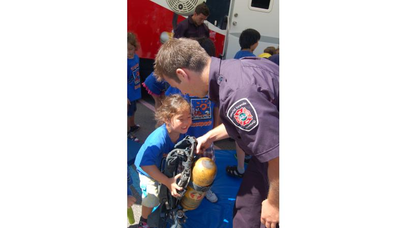 A young apprentice learns how heavy a firefighter's self-contained breathing apparatus is.