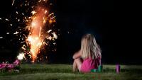 Une fillette regarde des feux d'artifices, dans un contexte domestique.