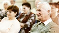 Des personnes âgées assistent à une conférence.
