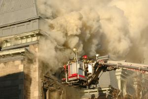 Firefighters work to put out a fire on top of a building