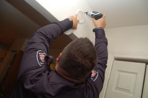 Prevention officers installs a smoke detector