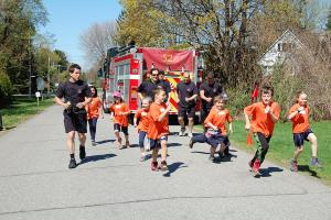 Firefighters run with children