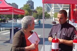 A prevention officer shares fire safety tips with a resident duing Fire Prevention Month.