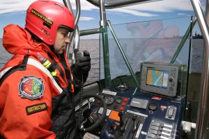 A fireman-rescue worker in a boat during a marine rescue simulation