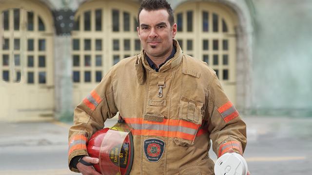 Capitaine de pompier avec un avertisseur de fumée en main.