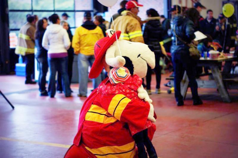 Enfant dans les bras de la mascotte Chef