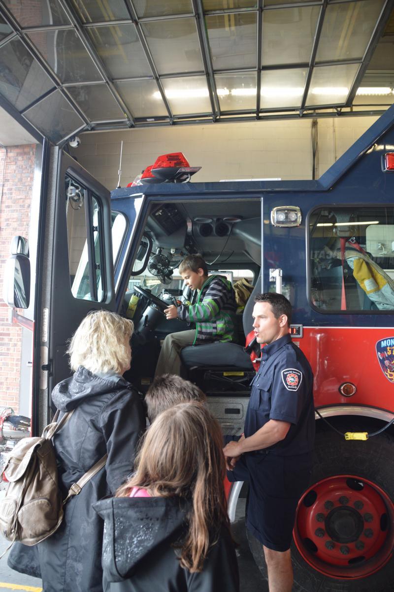 Des citoyens discutent avec un pompier du SIM lors d'une visite en caserne.