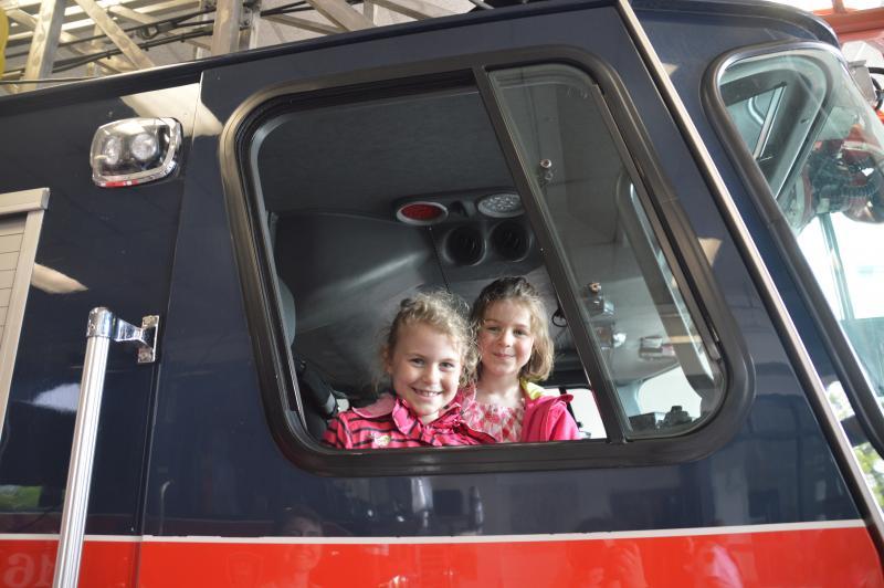 Des enfants sont assis dans un véhicule du SIM lors d'une visite en caserne.