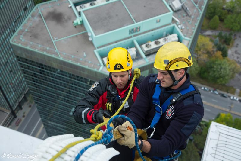 Two firefighters on top of a building during a high altitude rescue simulation