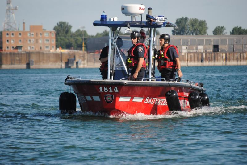Firefighters-rescue workers in a boat during a marine rescue simulation