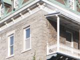 L'aile 1881 comporte une galerie sur sa façade latérale. Elle est entourée de cours et de stationnements. Photographie.