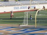 Des gradins en béton sont aménagés sur les talus bordant le terrain de sport. Photographie.