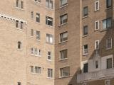 Vue de la cour intérieure des appartements Gleneagles. On remarque le parement en pierre de moellon du soubassement de l'immeuble, ainsi que la sortie ogivale menant à la voie de circulation publique. Photographie.