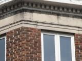 Le couronnement du Rockliffe, avec sa corniche à modillons et ses composantes moulées intégrées au parement de brique, qui imitent une balustrade.