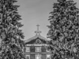 Façade du Collège de Montréal l'hiver, surmontée d'une croix. Deux sapins enneigés encadrent la façade.