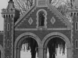 Le portail d'entrée du cimetière Notre-Dame-des-Neiges en hiver; il est entièrement en pierre, et comporte quatre ouvertures cintrées, deux massifs de maçonnerie aux extrémités et un élément central en forme de fronton surmonté d'une croix.