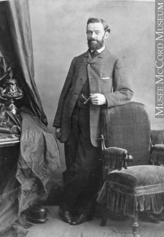 Portrait en pied d'Henri-Maurice Perrault, debout, appuyé au dossier d'un fauteuil.