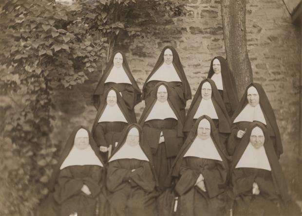 Un groupe de 11 Religieuses Hospitalières de Saint-Joseph de Montréal disposées en rangées pose dans le jardin du monastère en 1903.