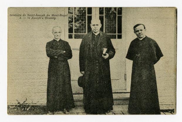 Trois membres de la congrégation de Sainte-Croix photographiés en pied devant une porte de l'Oratoire Saint-Joseph.