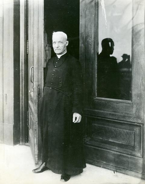 Le frère André debout à la porte de la crypte de l'Oratoire.