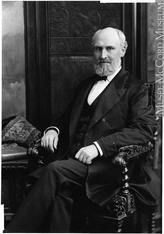 Portrait de William Macdonald, assis sur un fauteuil, jambes croisées.