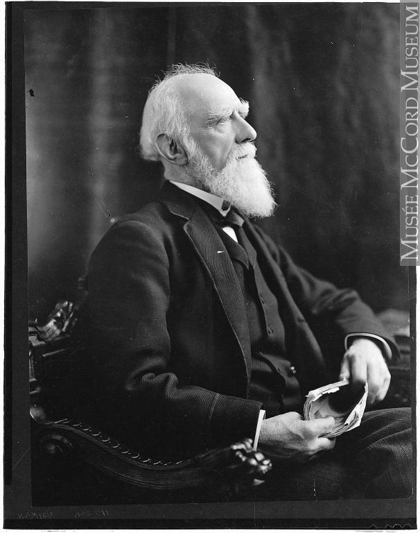 Portrait de profil de Donald Smith, assis dans un fauteuil et tenant un document dans ses mains.