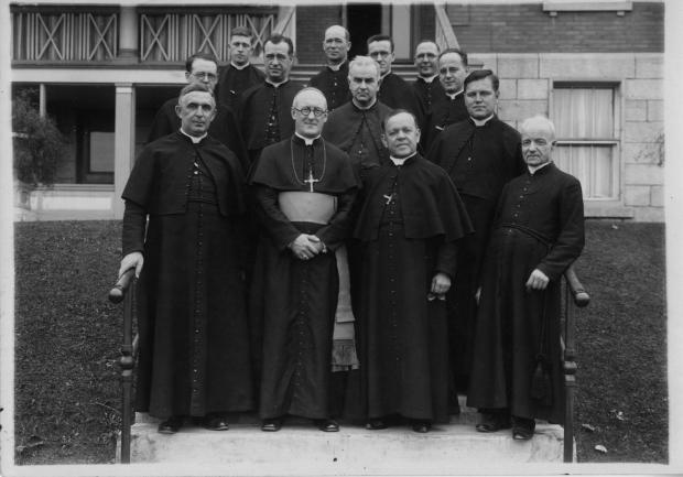 Un groupe de religieux de Sainte-Croix pose en rangées devant un édifice.