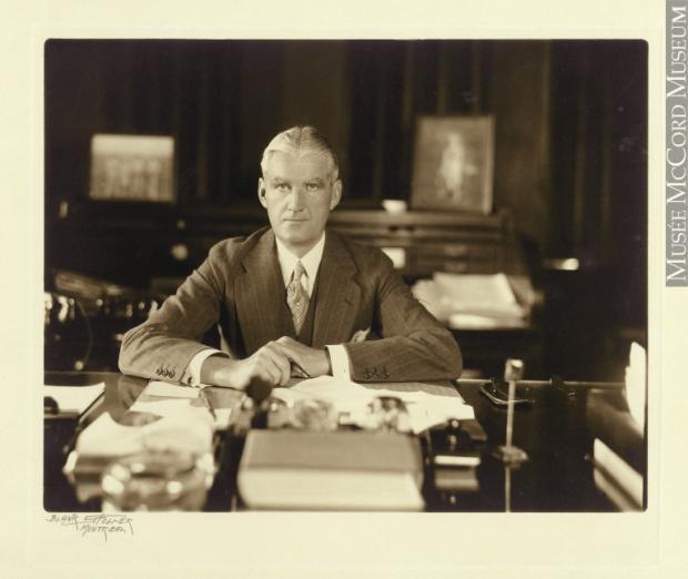 Portrait de John W. McConnell assis à son bureau, les deux bras appuyés sur la table de travail parsemée de documents et de livres. En arrière-plan, on voit un secrétaire et deux portraits au mur.