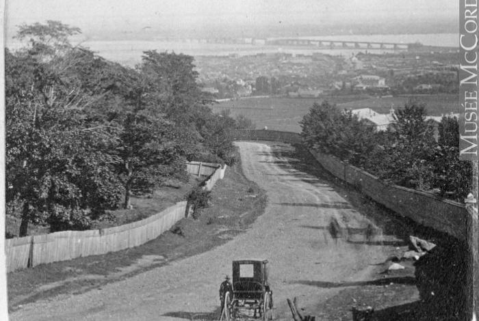 """""""Vue de Montréal depuis la barrière de péage du chemin de la Côte-des-Neiges, QC, 1859"""". Photographie en noir et blanc."""