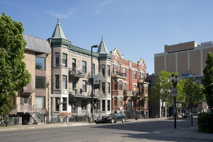 Les appartements Carrière étaient mitoyens des deux côtés. Aujourd'hui, le bâtiment l'est seulement du côté gauche. La façade est recouverte de brique rouge, sauf au niveau du soubassement qui est en pierre de taille. Photographie.