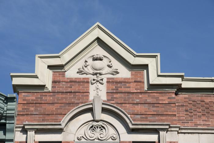 Détail du couronnement du bâtiment situé au 115-119, avenue du Mont-Royal Ouest. Photographie.