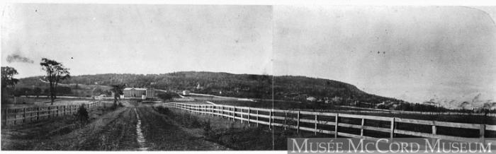 Le Séminaire des Sulpiciens apparaît au bout d'un chemin clôturé. Derrière, un chemin en diagonale traverse la montagne boisée.