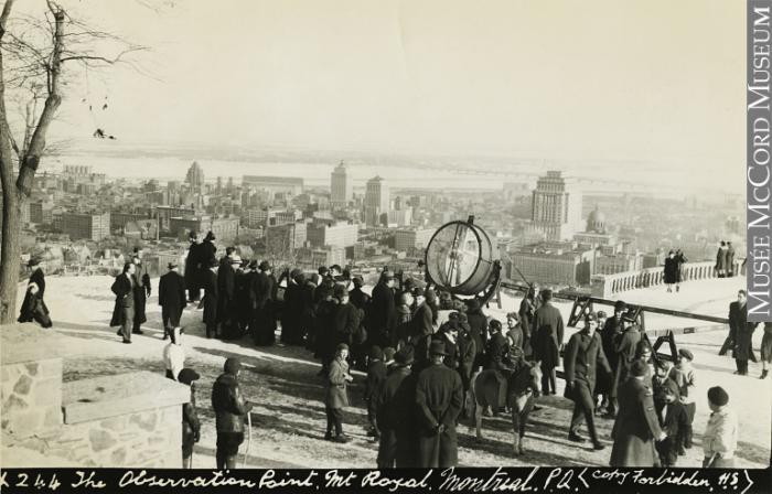 Sur le belvédère du Mont-Royal, une foule admire la vue sur le centre-ville, où on voit les gratte-ciel de l'époque, et le fleuve au loin.