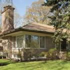 Vue d'angle de la maison E. Dossin montrant notamment le toit en croupe recouvert de tuiles d'argile et dominé par une imposante cheminée. Photographie.