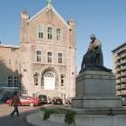La façade monumentale de l'ancien dispensaire rappelle l'architecture des églises néo-romanes. Au centre de la cour d'honneur est érigée une statue de Jeanne Mance. Photographie.