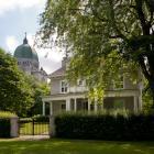 Élévation principale de la maison Marcel-Taillefer. Située en contrebas de l'Oratoire Saint-Joseph, elle prend place sur un terrain gazonné où se trouvent des arbres matures. Photographie.