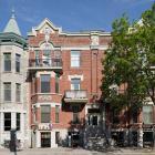 Vue des appartements Carrière montrant notamment la composition symétrique de la façade ponctuée de baies et de balcons répartis de part et d'autre de l'axe central et couronnée d'un parapet surmonté de deux frontons. Photographie.
